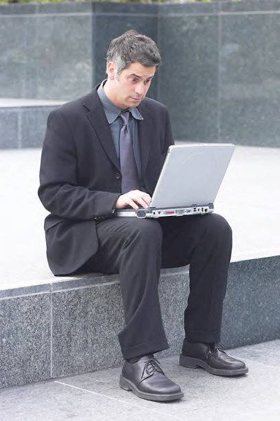 man using laptop in public looking confused
